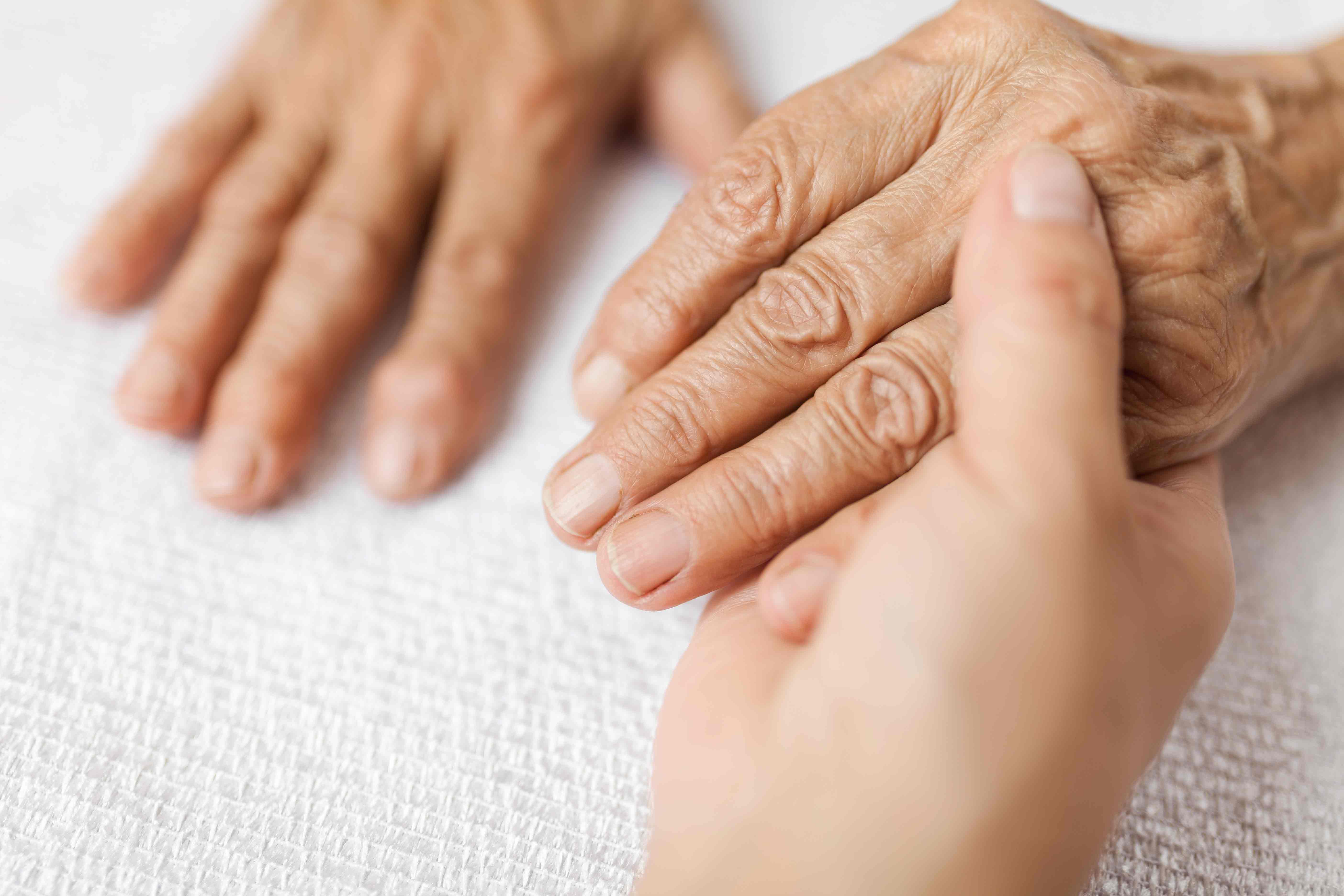 Caregiver Holding Elderly Woman's Hand - Memory Care Home Solutions - Family Caregiver Training